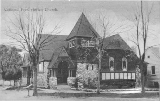 Black and white image of small church building with stone wood siding